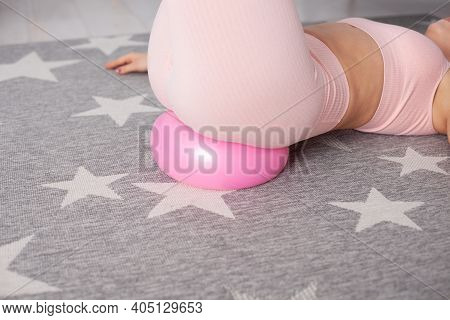 Close-up Woman Sports Booty In Pink Pants Lying On A Rubber Flattened Pilates Ball On A Gray Carpet