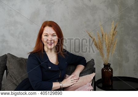 Classic Portrait Of Seated Woman With Red Hair On Dark Gray Background. Woman's Smile. Minimalistic