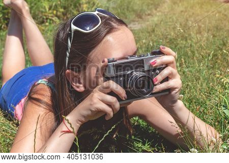 Young Beautiful Woman Holding Retro Camera In Her Hands Lying On The Lawn. Photographing In Nature.