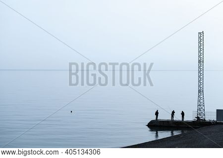 Yalta, Crimea - May 8, 2018: Fishermen Are On A Pier In Yalta Resort Town At Evening, Silhouette Pho