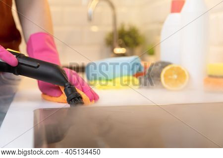 Women In Rubber Gloves Cleaning Black Ceramic Cooktop Side With A Hot Steam Cleaner And Cleaning Pro