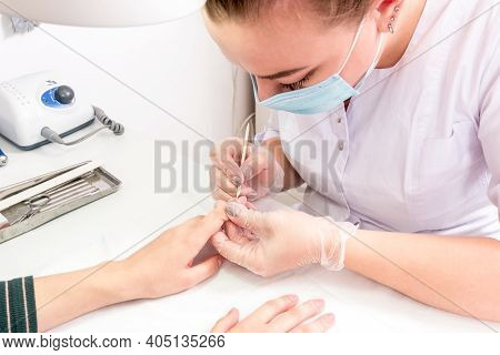 The Process Of Creating A Beautiful And Neat Manicure. The Manicurist Processes Clints Nails With A