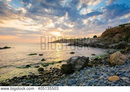 Dramatic Sunrise At The Sea. Beautiful Seascape With Clouds On The Sky Above Horizon. Rocks And Pebb