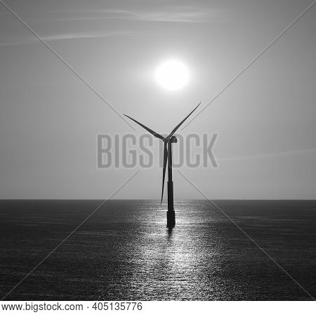 Backlit Offshore Turbine With Intense Sun At Dawn, Black And White