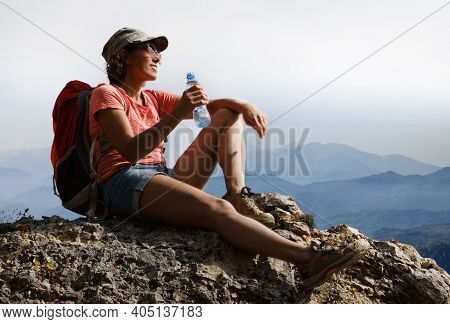 Female Tourist Drinking Water On Top Of A Hill In Silence And Loneliness Admires A Tranquil Natural