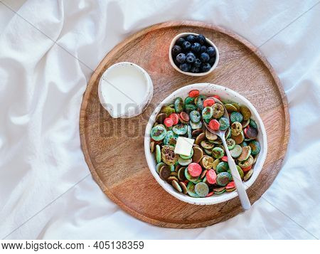 Trendy Food - Pancake Cereal. Bowl Of Colorful Mini Cereal Pancakes On Wooden Tray Over Bed. Tiny Pa