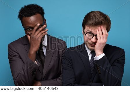 Feeling Depressed After Work. Exhausted Young Men Covering Face With Hand.