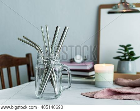 Metal Drinking Straws In Glass Bottle On White Marble Table Indoor. Metal Straws On Table In Living