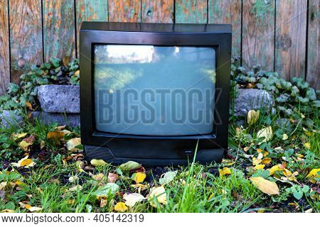 Old Analog Television Set On The Weathered Wooden Planks Background