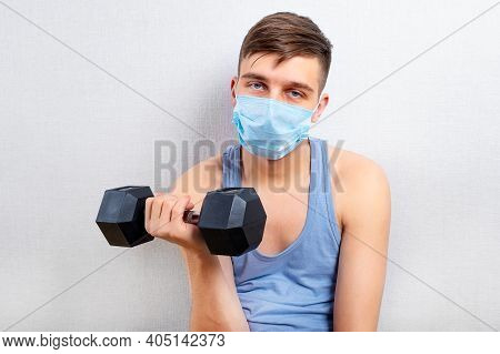 Sad And Weak Young Man In Flu Mask Hold A Dumbbell By The White Wall