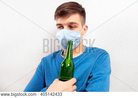 Sad Young Man In Flu Mask With A Beer By The Wall In The Room