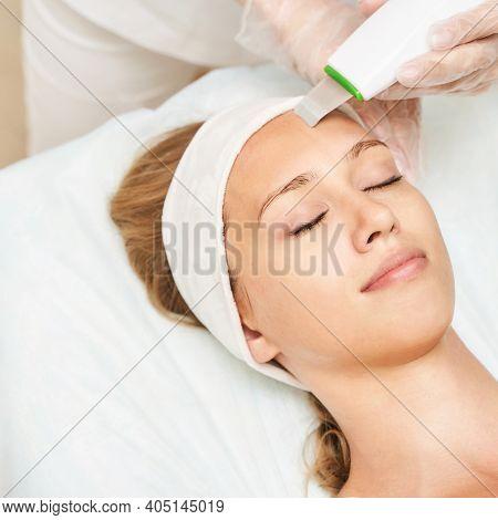 Ultrasonic Skin Equipment. Woman Face Cosmetology Treatment. Female Clinic Facial Procedure. Anti Ac