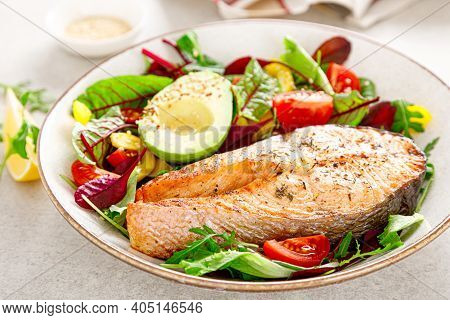 Salmon Fish Steak Grilled, Avocado And Fresh Vegetable Salad With Tomato, Bell Pepper And Leafy Vege
