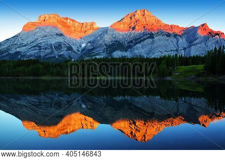 Golden Sunrise Reflecting Off The Calm Waters Of Wedge Pond Beneath Mount Kidd In The Kananaskis Cou