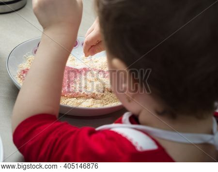 Child Covering Pork Meat With Breadcrumbs In The Kitchen