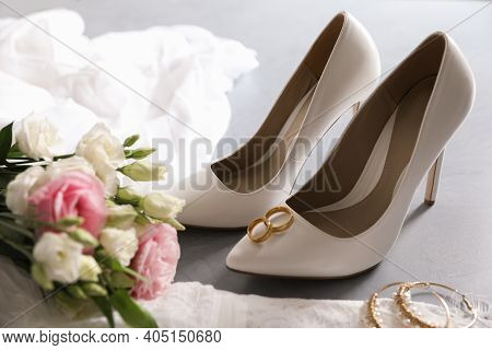 Composition With Wedding Dress, White High Heel Shoes And Rings On Grey Background