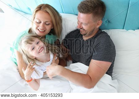 Parents With Child Indulge And Cuddle In Bed. What Is Use Of Parental Hugs For Child Concept