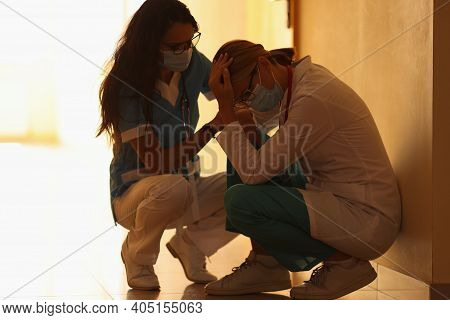 Two Frustrated Doctors In Medical Protective Masks Sit In Corridor Of Hospital. Irregular Working Ho