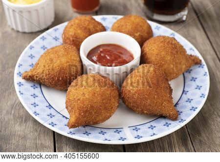 Typical Brazilian Snack Coxinha On A Plate Over Wooden Table.