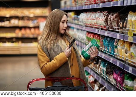 A Young Woman Scans The Product With An App In Her Smartphone.