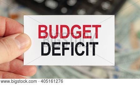 Motivational Words: Budget Deficit. Man Holds A Piece Of Paper With The Text: Budget Deficit. Busine