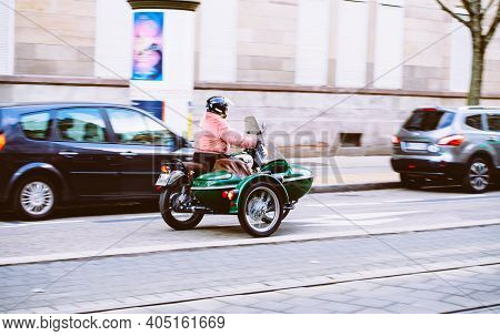 Strasbourg, France - Feb 14, 2019: Side View Of Woman In Pink Coat Driving A Green Mash Motorcycle W