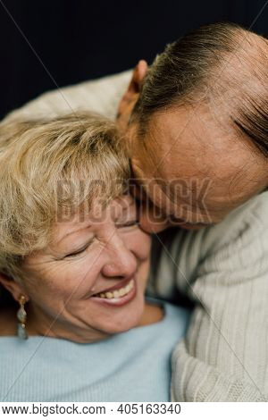 Portrait Of Old Couple Wife And Husband Hugging And Smiling. Dark Blue Background. Happy Lovers On R