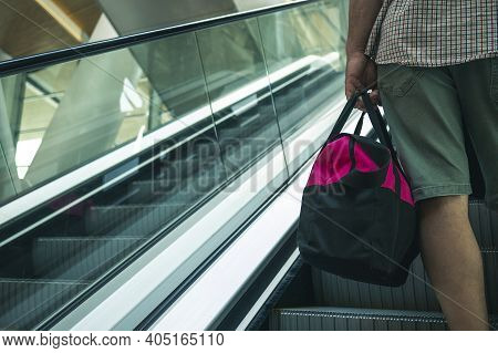 A Man With A Bag On A Trip Is Understood On The Escalator. A Man Holding A Pink Bag And Riding An Es