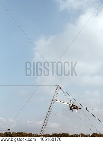 Dnipro, Ukraine  - 10.12.2020: Two Construction Workers Climbers Hanging Up On Crane Cabin To Instal