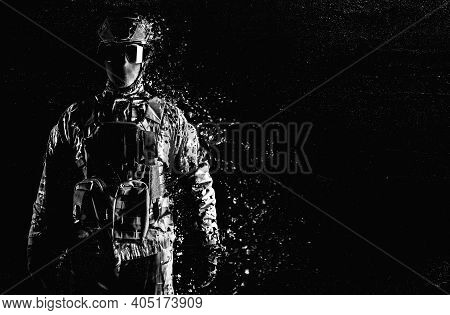 Black And White Photo Of A Fully Equipped Soldier Standing In Tactical Clothing And Dissolving On Gr