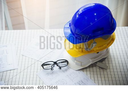 Close-up White, Yellow And Blue Hard Safety Helmet Hat For Safety Project Of Workman As Engineer Or