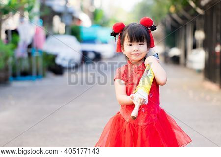 Asian Cute Girl Walking Carrying A Yellow Umbrella, She Was Wearing A Bright Red Chinese Dress. Chil