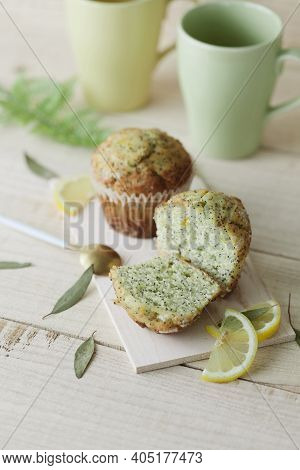 Lemon Poppy Seed Muffins On Wooden Tray With Yellow And Green Cups, Slices Of Lemon And Eucalyptus L