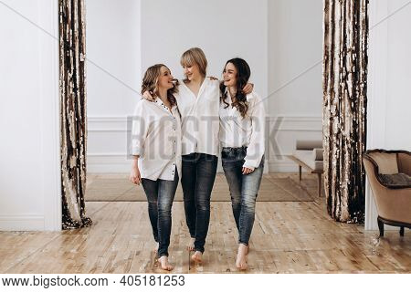 Three Young Women Walk Together And Hug Indoors. Portrait Of Three Ladies, Girlfriends. 3 Sisters To