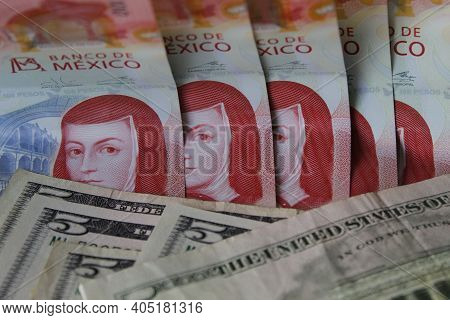Approach To Mexican Banknotes Of 100 Pesos And American Five Dollars Bills