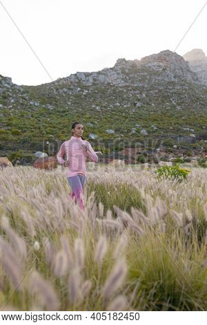 Fit african american woman in sportswear running through tall grass. healthy lifestyle, exercising in nature.