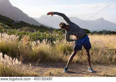 Fit african american man in sportswear stretching in tall grass. healthy lifestyle, exercising in nature.