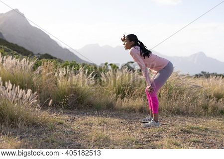 Fit african american woman in sportswear resting leaning on knees in tall grass. healthy lifestyle, exercising in nature.