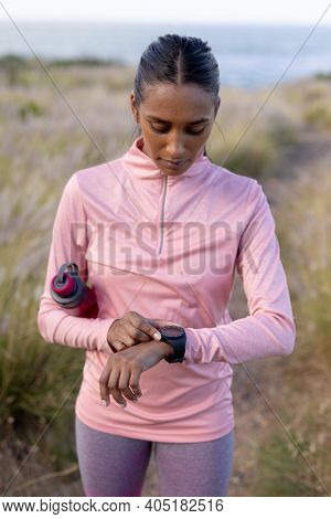 Portrait of fit african american woman in sportswear using smartwatch holding water in tall grass. healthy lifestyle, exercising in nature.