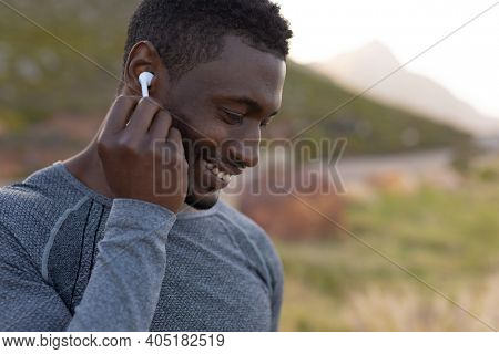 Portrait of fit african american man in sportswear putting earphones in in tall grass. healthy lifestyle, exercising in nature.