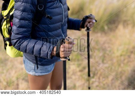 Fit african american woman wearing backpack nordic walking on coast. healthy lifestyle, exercising in nature.