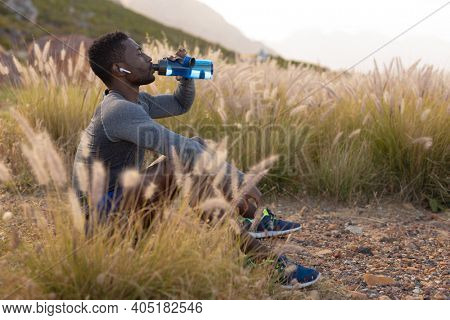 Portrait of fit african american man in sportswear resting drinking water in tall grass. listening to music with earphones in. healthy lifestyle, exercising in nature.