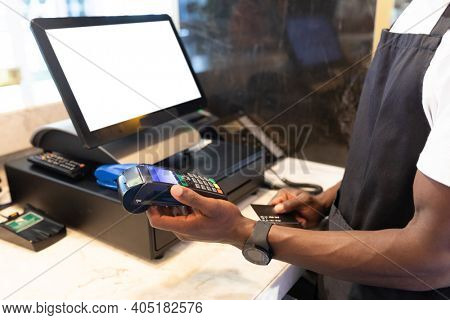 African american male barista using costumers creditar card for payment in a cafe. independent small business owner.
