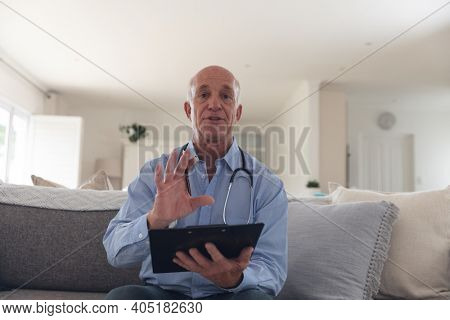 Senior caucasian male doctor having a video call using a digital tablet at home. medical professional worker.
