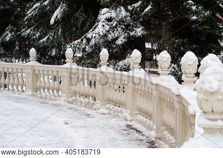 Snow Covered Round Veranda With White Stone Balusters