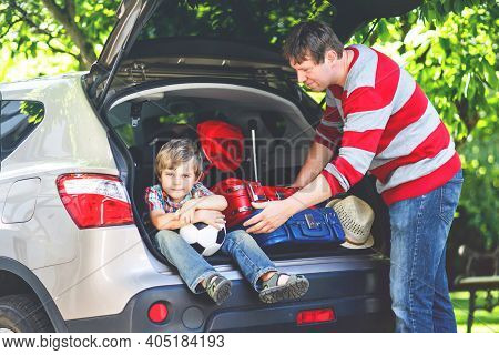 Little Kid Boy Sitting In Car Trunk Just Before Leaving For Summer Vacation. Dad Packing Suitcases.