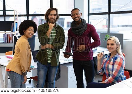 Diverse group of business people working in crative office. portrait of group of people looking at camera and smiling. business people and work colleagues at a busy creative office.