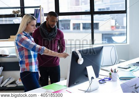 Two diverse business people working in creative office. man and woman using desktop computer. business people and work colleagues at a busy creative office.