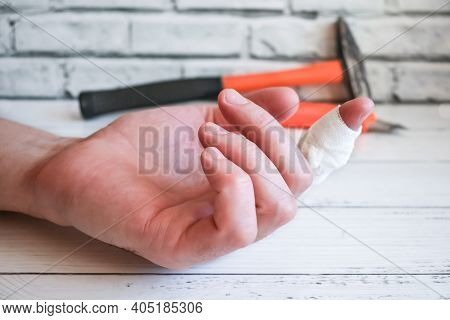 Bandaged Finger On Hand Of Master. An Accident At Work - Bandaging Man's Injured Finger. Hand With B