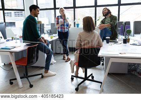 Diverse group of business people working in creative office. group of people in meeting discussing work. business people and work colleagues at a busy creative office.